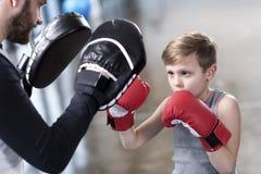 Chłopiec boksera ćwiczy poncze z trenerem Fotografia Royalty Free