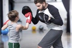 Chłopiec boksera ćwiczy poncze z trenerem Fotografia Stock