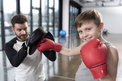 Chłopiec boksera ćwiczy poncze z trenerem Obraz Royalty Free