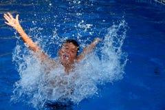 Chłopiec bryzga w pływackim basenie zdjęcia stock