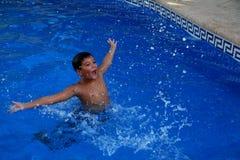Chłopiec bryzga w pływackim basenie obraz stock