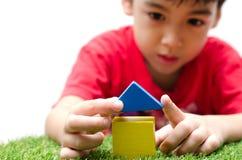 Chłopiec buduje małego dom z kolorowymi drewnianymi blokami zdjęcie royalty free