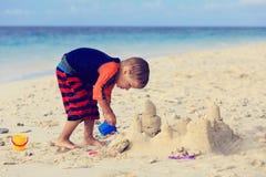 Chłopiec budynku piaska kasztel na plaży zdjęcia stock