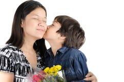 Chłopiec całuje jego matki z kwiatem Zdjęcie Royalty Free