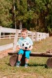 Chłopiec chirliderka siedzi z futbolem na polu na ławki dopatrywania futbolu zdjęcia royalty free