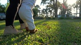 Chłopiec chodzący pierwsi kroki z mamą outside zbiory wideo