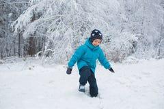 Chłopiec chodzi w śniegu w zima parku Zdjęcia Royalty Free