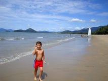 Chłopiec chodzi wzdłuż pięknej plaży australijczyka wybrzeże zdjęcie stock