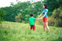 Chłopiec chodzi z jego matką w łące Obrazy Royalty Free