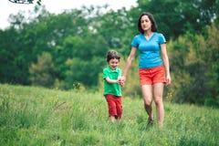 Chłopiec chodzi z jego matką w łące Zdjęcia Royalty Free
