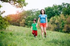 Chłopiec chodzi z jego matką w łące Fotografia Royalty Free