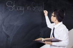 Chłopiec chwyty rezerwują z teksta pobytem w szkole Obrazy Stock