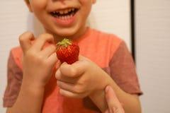 Chłopiec chwyty w jego wręczają czerwonej truskawki fotografia royalty free