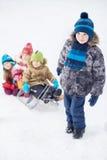 Chłopiec ciągnie saneczki z młodymi dziećmi Zdjęcia Stock