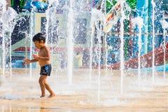 Chłopiec cieszy się bawić się z podłogową wodną fontanną przy Cartoon Network zdjęcia royalty free