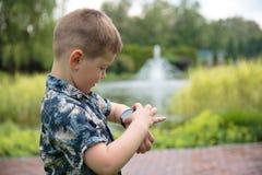 Chłopiec considering zegarek na ręce zdjęcie royalty free