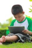 chłopiec cyfrowy pastylki używać zdjęcia stock