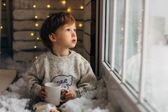 Chłopiec czekanie dla Santa klauzula Śliczny kędzierzawy berbeć chłopiec obsiadanie blisko okno zdjęcia stock