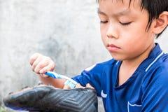 Chłopiec czyści jego stadniny po dopasowania Rozumie to i Fotografia Royalty Free