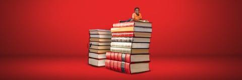 Chłopiec czytanie na stosie książki z czerwonym tłem zdjęcia royalty free