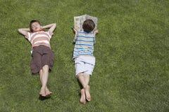 Chłopiec czytanie Oprócz Uśpionego brata Na trawie Obraz Royalty Free