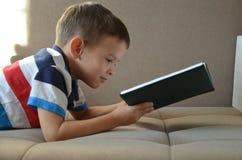 Chłopiec czytelnicza książka na podłoga w domu obraz royalty free