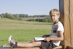 Chłopiec czytelnicza książka przy lato tarasem Przypadkowi ubrania w kontekście niebieskie chmury odpowiadają trawy zielone niebo Zdjęcia Royalty Free