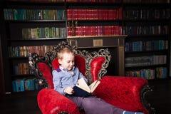 Chłopiec czytelnicza książka w domu Obraz Stock