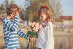 Chłopiec daje dziewczyna bukietowi kwiaty zdjęcie royalty free