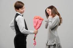 Chłopiec daje kwiaty dziewczyna zdjęcia royalty free