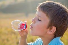 Chłopiec dmuchanie w górę mydlanych bąbli - Zdjęcie Royalty Free