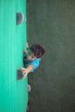 Chłopiec dojechania pięcia chwyty na zieleni ścianie fotografia royalty free