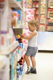 Chłopiec dopatrywania samochody w bawją się sklep Zdjęcie Stock