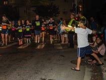 Chłopiec dosięga out zachęcać biegaczów Fotografia Royalty Free