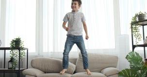 Chłopiec doskakiwanie na kanapie w domu zbiory