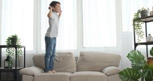 Chłopiec doskakiwanie na leżance w domu zbiory wideo
