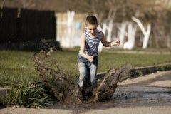 Chłopiec doskakiwanie w kałuży zdjęcie royalty free