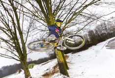 Chłopiec doskakiwanie z jego rowerem nad rampą w śniegu Obraz Royalty Free