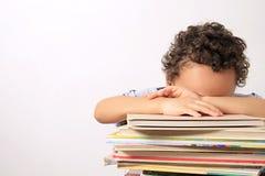 Chłopiec dosypianie na stosie książki Fotografia Stock