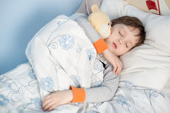 Chłopiec dosypianie w jego łóżku Zdjęcia Royalty Free