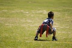 Chłopiec dzieciak bawić się chorągwianego futbol na otwartym polu Fotografia Royalty Free