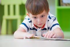 Chłopiec dzieciak kłaść puszek na podłoga i czytelniczej bajki książce w preschool bibliotece, dzieciniec edukaci szkolnej pojęci obrazy royalty free