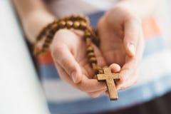 Chłopiec dziecka modlenie i mienie drewniany różaniec obraz royalty free