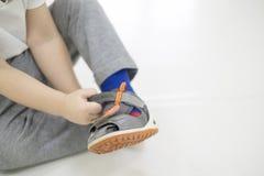 chłopiec dziecka ręka próba odizolowywał małego buta stawiającego lato próby biały Chłopiec z butami w ręce dlaczego wybierać but fotografia stock