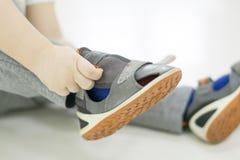 chłopiec dziecka ręka próba odizolowywał małego buta stawiającego lato próby biały Chłopiec z butami w ręce dlaczego wybierać but obrazy royalty free