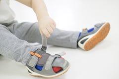 chłopiec dziecka ręka próba odizolowywał małego buta stawiającego lato próby biały Chłopiec z butami w ręce dlaczego wybierać but fotografia royalty free