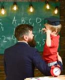 Chłopiec, dziecko dyskutuje skrobaniny na chalkboard w magisterskiej nakrętce podczas gdy nauczyciela słuchanie Prodigy dziecka p zdjęcia stock