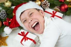 Chłopiec dziecko ma zabawę z boże narodzenie dekoracją, twarzy wyrażeniem i szczęśliwymi emocjami ubierającymi, w Santa kapeluszu Zdjęcia Royalty Free