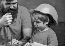 Chłopiec, dziecko ruchliwie w ochronnym hełma uczenie używać śrubokręt z tata Ojcuje, wychowywa z brodą uczy małego syna, obrazy royalty free