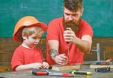Chłopiec, dziecko ruchliwie w ochronnym hełma uczenie używać śrubokręt z tata Remontowy i warsztatowy pojęcie Ojciec, rodzic zdjęcie stock